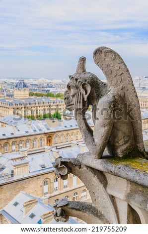 A gargoyle observes the city of Paris from its privileged position - stock photo