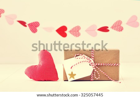 A garland of hearts above a small gift-wrapped box and red textile heart on a neutral white background with copyspace - stock photo
