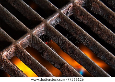 A gas grill with open flames below the rusty iron grate. - stock photo