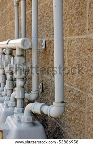A gas pipe connect meter on the yellow wall. - stock photo