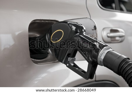A gasoline pump nozzle in the tank of an automobile. - stock photo