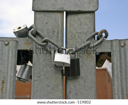 A gate secured with a chain and far too many padlocks! - stock photo