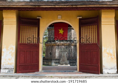 A gate with Vietnamese flag of Thien Mu pagoda in Hue, Vietnam - stock photo