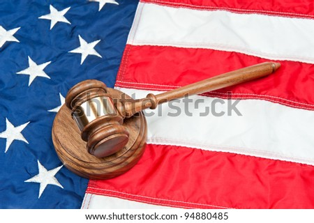 A gavel and sound block on an American flag representing the legal system and any law inference in the USA - stock photo