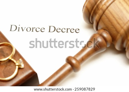 A gavel and wedding rings on top of divorce papers with the focus on the writing. - stock photo
