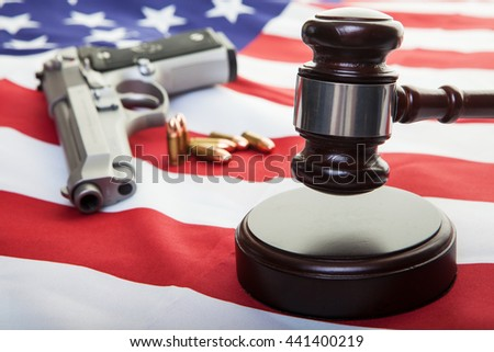 A gavel on an american flag with a gun and bullets in the background, focus on the gavel.