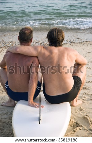 A gay male couple cuddle together while sitting on surfboard at the beach. - stock photo