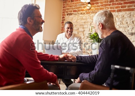 A gay male couple holding hands at a hotel check in desk - stock photo