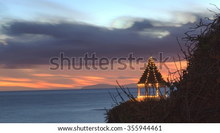 A gazebo on a cliff overlooking the ocean in Laguna Beach, California, lit with Christmas lights at sunset.  - stock photo