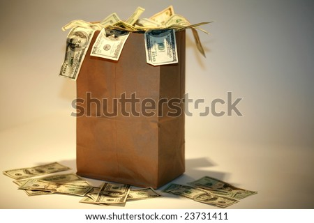 a Generic brown paper bag over flowing with Money - stock photo