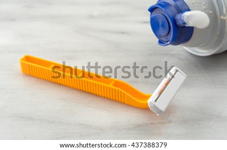 A generic disposable shaving razor with an empty can of foam on a marble counter top. - stock photo