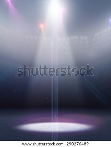 A generic ice rink stadium with a frozen surface under an illuminated floodlight - stock photo