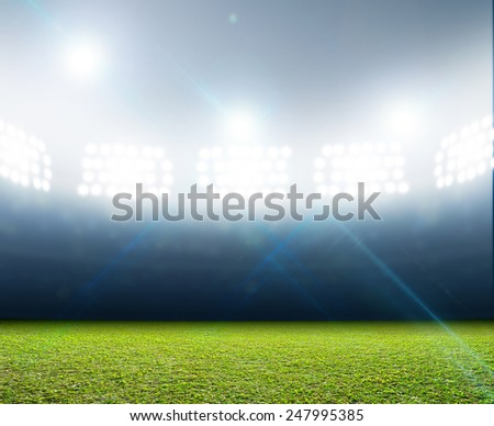 A generic stadium with an unmarked green grass pitch at night under illuminated floodlights - stock photo