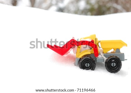 A Generic Toy Snow Plow on a Bed of White Snow with Trees in the Distant Background, Room for Text - stock photo