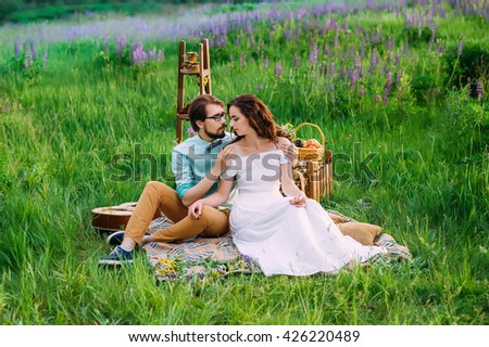 a gentle embrace of an enamored couple having a romantic picnic outdoors