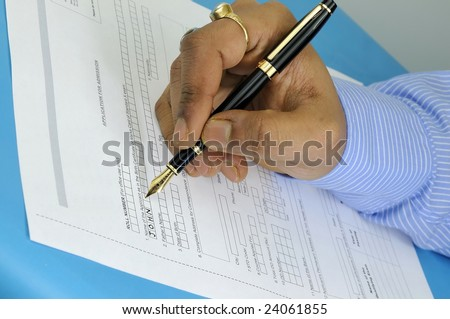 a gentleman filling up an application form for admission with a fountain pen - stock photo
