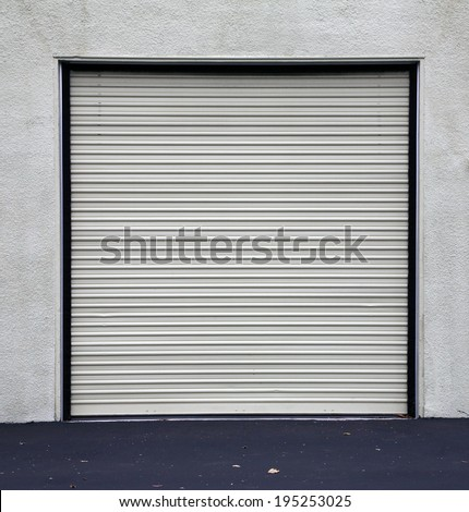 A Genuine Aluminum Warehouse Garage Roll Up Door and Entrance Door. Many Warehouses and Office Buildings have Roll Up Garage Doors to make it easy to store vehicles and gain access to products. - stock photo
