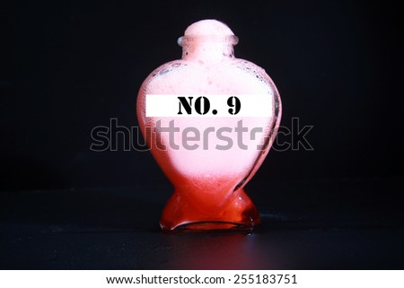 A Genuine Secret Recipe Love Potion in a Heart Shape Bottle isolated on black with room for your text - stock photo