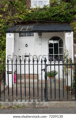 A Georgian Front door and porch with arched window and a front garden enclosed by Iron Railings on The Thames Path at Chiswisck - stock photo