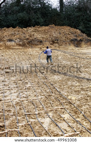 A geothermal heating system is built. The heating pipes are laid into the ground. - stock photo