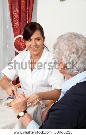 A geriatric nurse helping senior at breakfast - stock photo