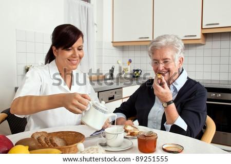 a geriatric nurse helps elderly woman at breakfast. elder care of seniors - stock photo