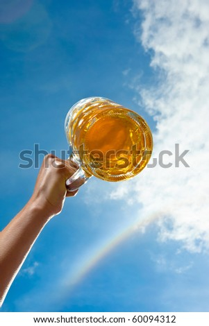 A german beer on a backdrop of blue sky and white clouds and authentic rainbow. - stock photo