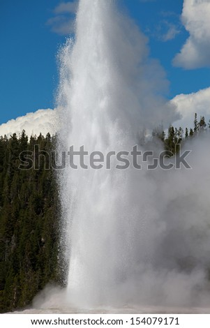 A geyser in Yellowstone National Park begins to erupt - stock photo