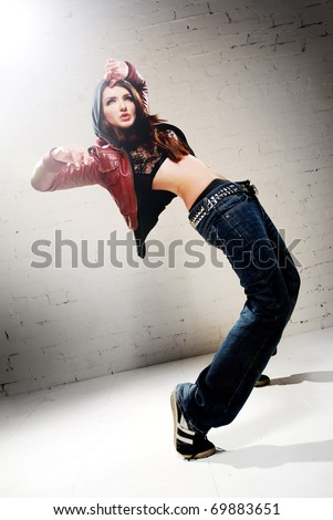 A ghetto styled girl dancing in front of brick wall
