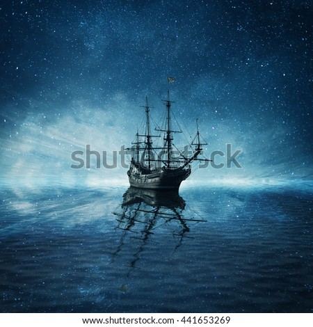 A ghost pirate ship floating on a cold dark blue sea landscape with a starry night sky background and water reflection. - stock photo