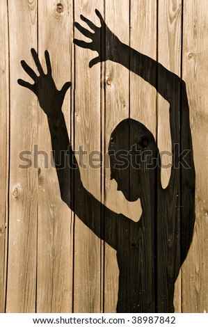 a ghost shadow or silhouette of a woman against a wooden fence with working path - stock photo
