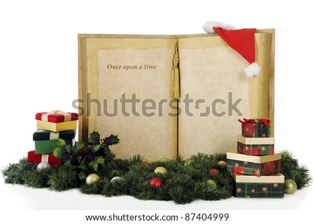 """A giant book with the words, """"Once upon a time..."""" with plenty of space for your copy.  The books is surrounded by Christmas gifts, decor and Santa's hat.  On a white background. - stock photo"""
