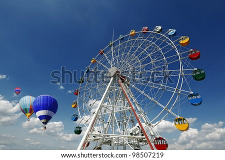 A giant colorful ferris wheel in an amusement park with colorful hot air balloons floating in the horizon on a blue cloudy day.