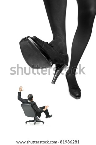 A giant foot about to squish a businessman in a chair isolated on white background - stock photo