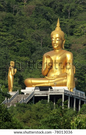 A giant golden Buddha statue in forest - stock photo