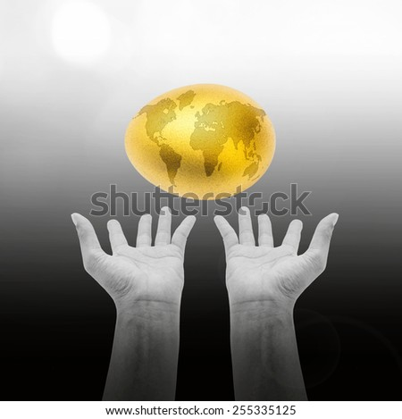 A giant golden egg dropping on two hands: a golden egg opportunity concept of fortune and a chance to be rich: Easter egg with world map - stock photo