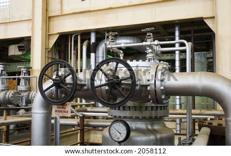 a giant pressure valve in a decommissioned electrical power plant - stock photo