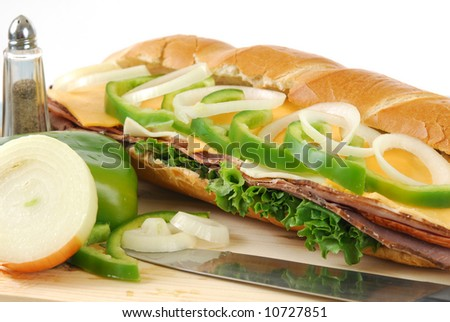 A giant sandwich loaded with cold cuts, onions, and peppers