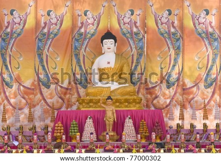 A giant statue of Buddha sits in Sydney's Darling Harbour precinct during Buddha's Birth Festival program. The symbol on the chest of the statue is a Buddhist religious sign and not the swastika. - stock photo