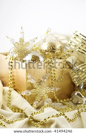 A gift box full of elegant gold Christmas decorations, vertical with copy space, on white background