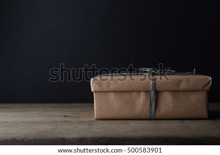 A gift box, in plain brown paper wrapping with dark grey raffia ribbon on oak table, with black chalkboard background providing copy space.