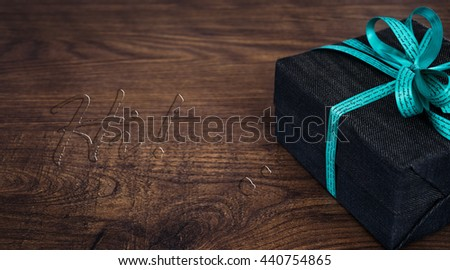 A gift box on wooden board with HI water drop text. - stock photo