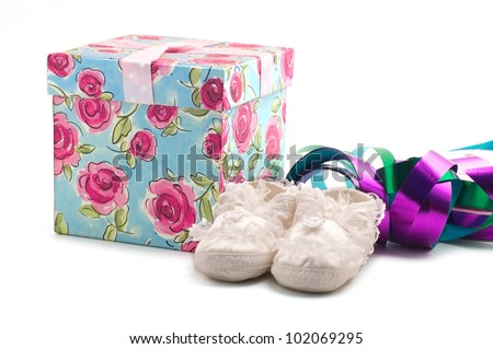 A gift box, ribbons and baby shoes - stock photo