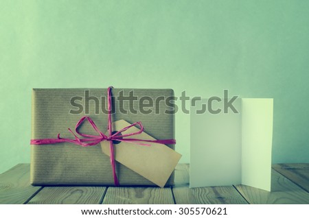 A gift box with blank label, wrapped in brown paper and tied with pink raffia bow on a wooden table.  An opened, blank  greeting card faces front.  Cross processed to give a retro or vintage style. - stock photo