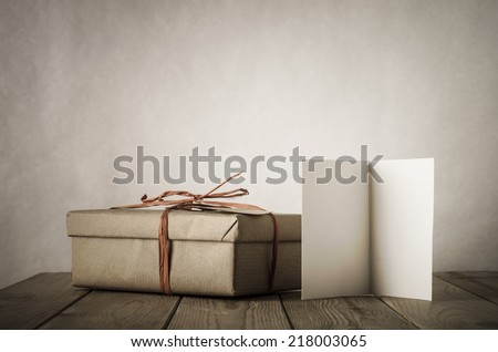 A gift box wrapped in brown paper and tied with raffia, angled and placed next to an open card left blank for copy space, on an old, worn and scratched planked table.  Earthy colours, vintage style. - stock photo