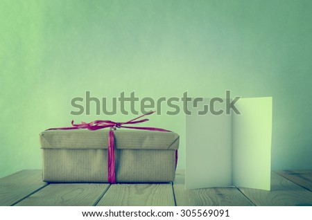 A gift box, wrapped in simple brown paper and tied with pink raffia bow on a wooden table. An opened greeting card faces front, left blank for text.  Cross processed to give a retro or vintage style. - stock photo