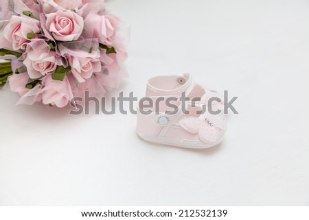 A gift for the newborn and mother. Pink flowers and children's sandals on the white bed - stock photo