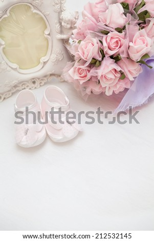 A gift for the newborn and mother. Pink flowers, photo frame and children's sandals on the bed. - stock photo