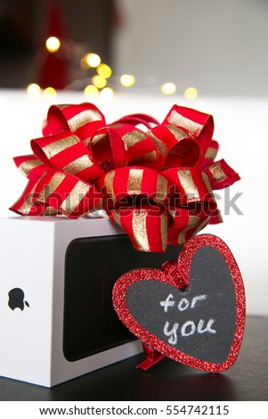 A gift on Valentine's Day. Red with gold bow. Box from phone. Iphone. Apple. Red heart with text For you