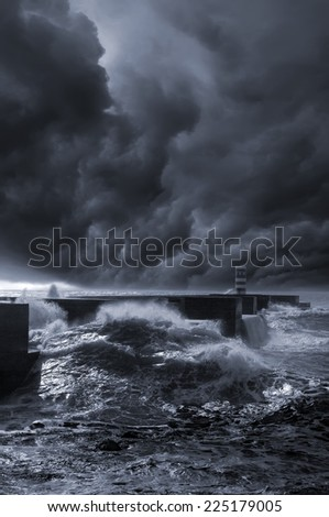 A gigantic storm with super cells formation at the entrance of a sea harbor. - stock photo